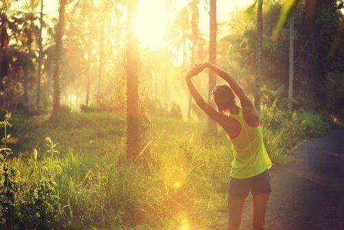 Mujer estirándose antes de salir a correr por la mañana