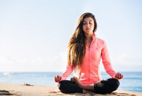 Mujer haciendo yoga en la playa para relajarse