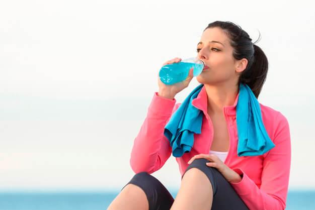Mujer sentada bebiendo una bebida energética