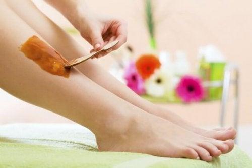Mujer depilándose las piernas con cera