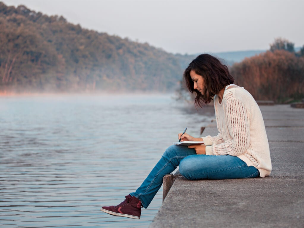 Mujer escribiendo en su diario emocional