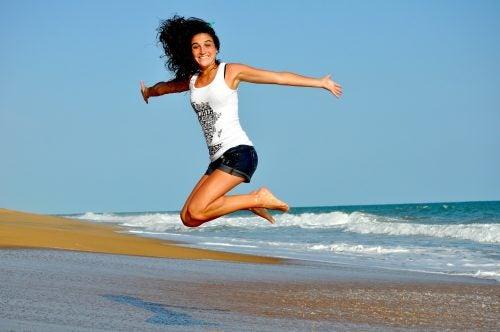 Mujer dando un salto en la playa