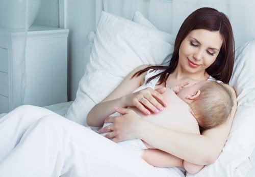 Mujer dando de mamar a su hijo.