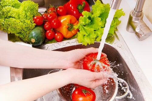 Mujer lavando tomates y verduras