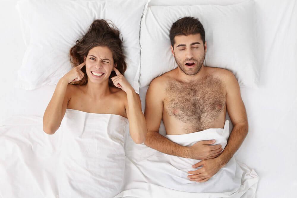 Mujer tapándose los oídos porque el hombre ronca