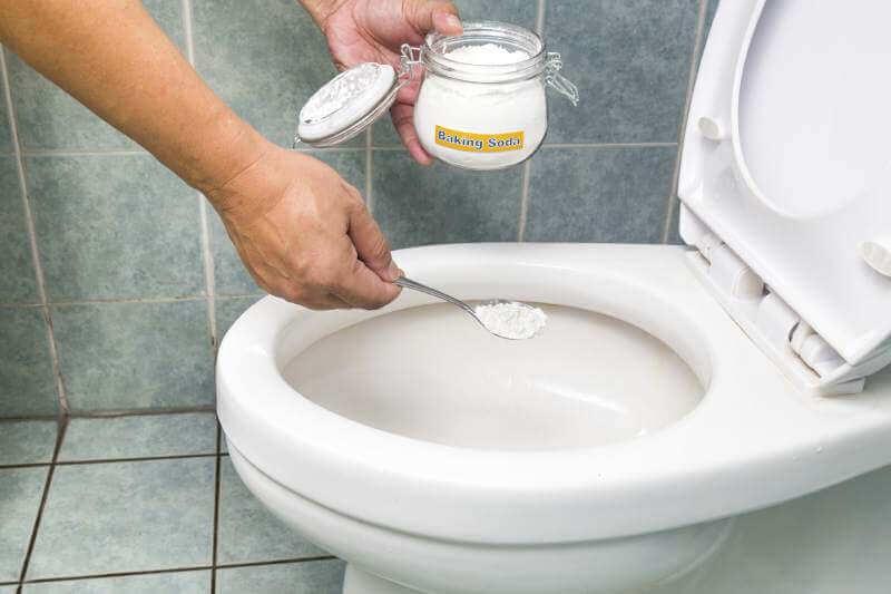 Persona hechando bicarbonato de sodio al inodoro.