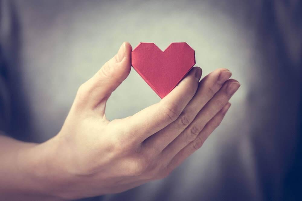 Mano con corazón rojo de papel