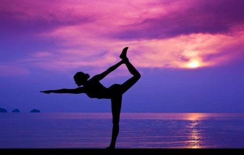 Mujer en una postura de yoga al lado de la playa