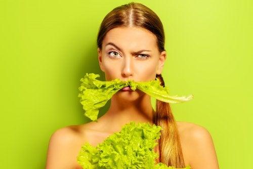 Mujer con lechuga en su boca