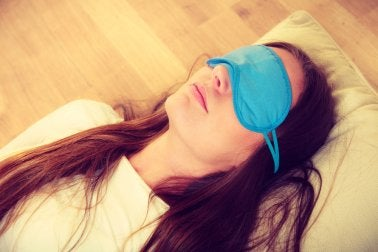 Mujer durmiendo con antifaz.
