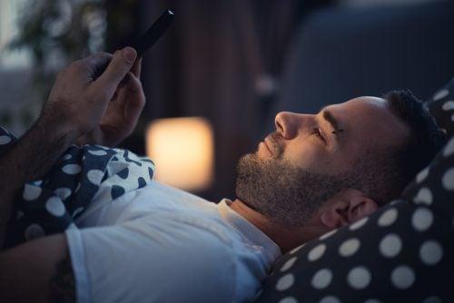 Hombre usando el móvil acostado