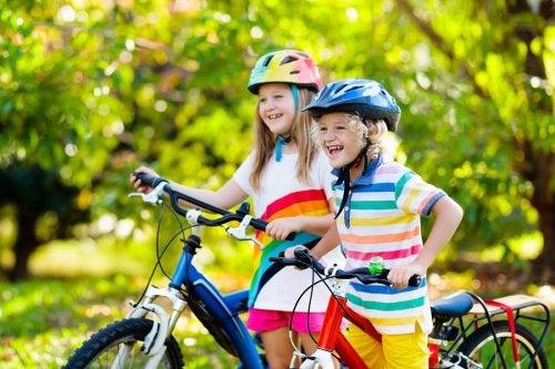 niños felices en un parque montando en unas bicicletas