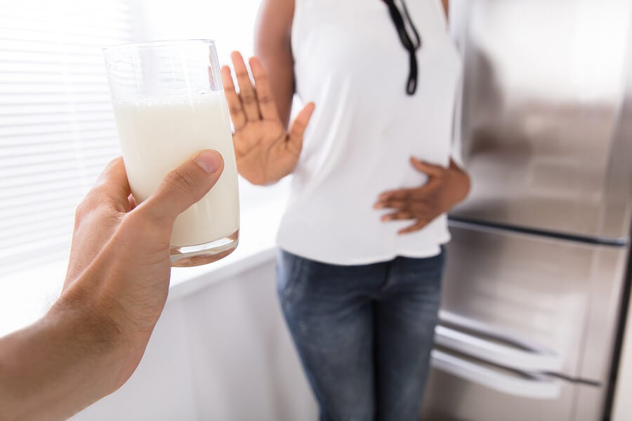 Mujer rechazando vaso de leche por intolerancia.