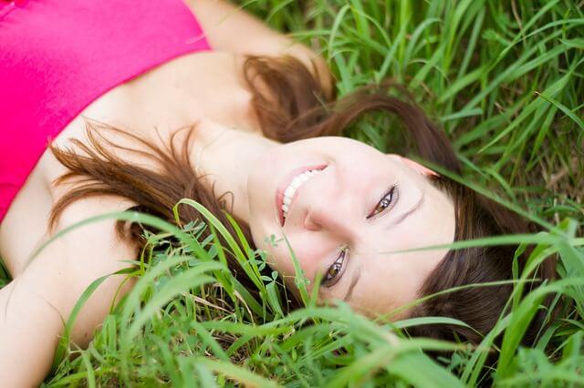 Mujer feliz acostada en el césped