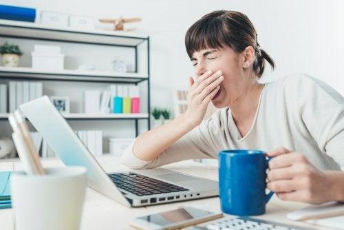 Mujer bostezando con una taza ante el ordenador.