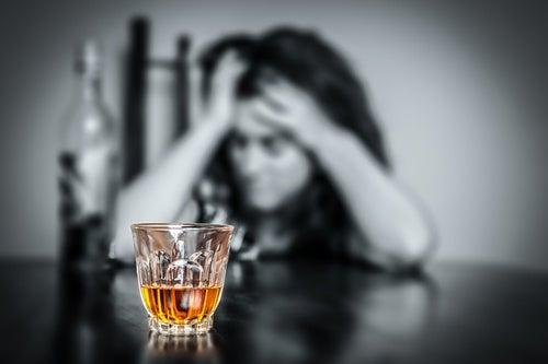 Mujer con dolor de cabeza frente a vaso de alcohol