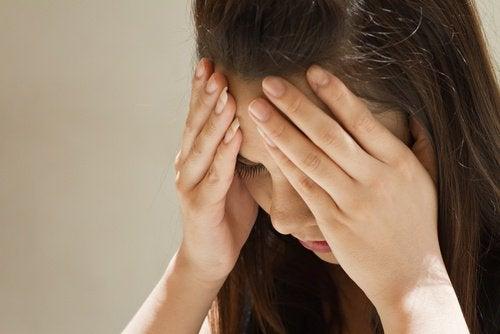 Variables psicológicas y cáncer: mujer estresada con las manos en la cabeza.