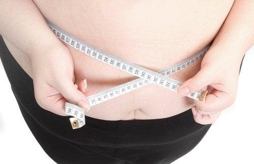 Persona obesa midiendo su cintura