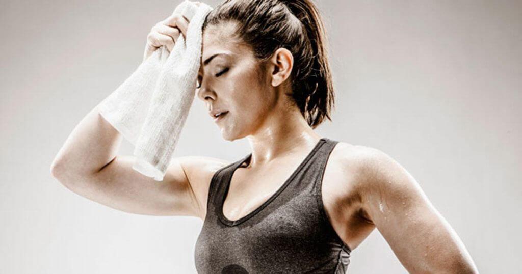 Mujer secándose el sudor de la frente con una toalla.
