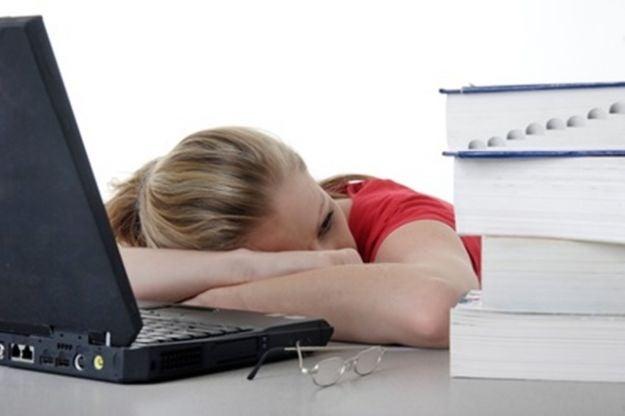 Mujer apoyada sobre la mesa, fatigada en el trabajo