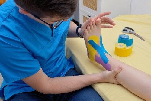 Fisioterapeuta aplicando un apósito neuromuscular.