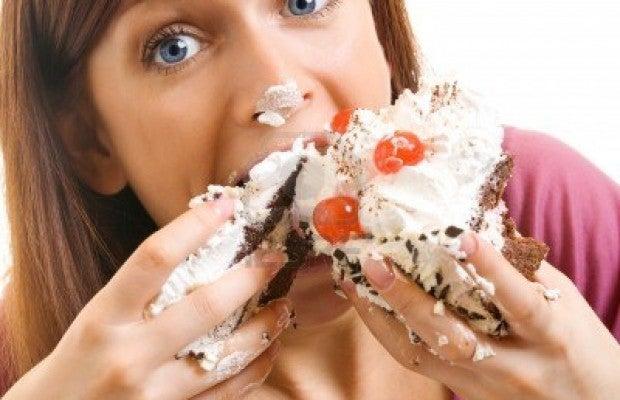 15025663-alegre-mujer-comiendo-pastel-aislado-sobre-fondo-blanco-620x400