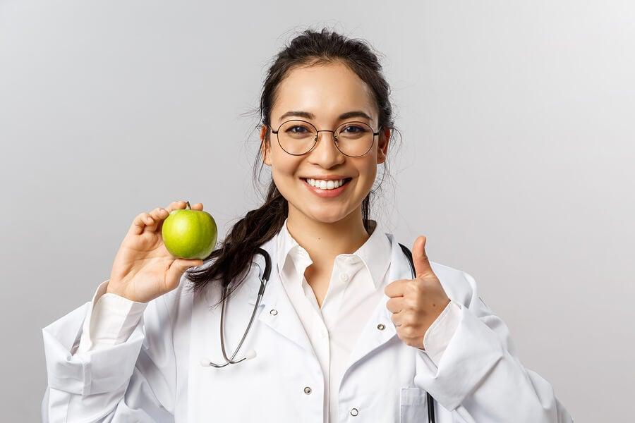 Doctora sosteniendo una manzana verde.