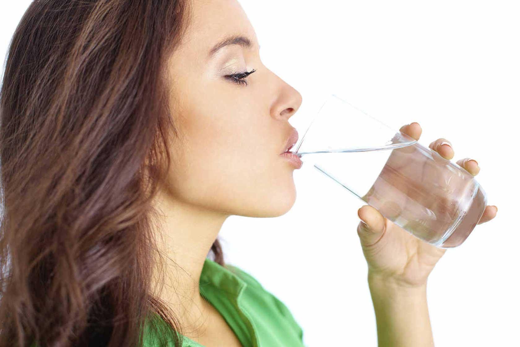 Mujer bebiendo agua de alcachofas.