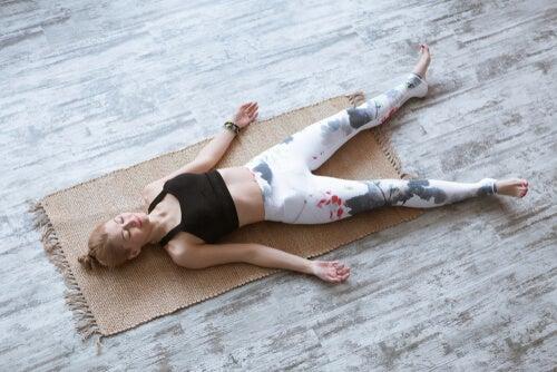 Mujer sobre manta de yoga, en postura soldado.