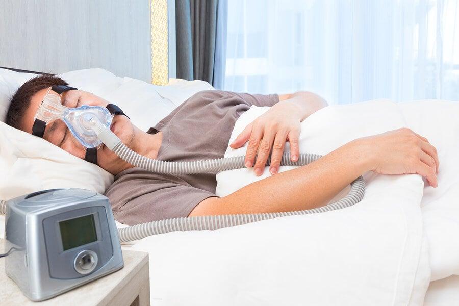 Paciente con apnea del sueño durmiendo con una máquina de aire.