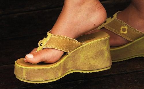 mujer con sandalias doradas