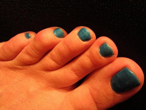 mujer con las uñas pintadas de azul