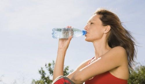 Mujer bebiendo agua para desintoxicarse después de hacer excesos