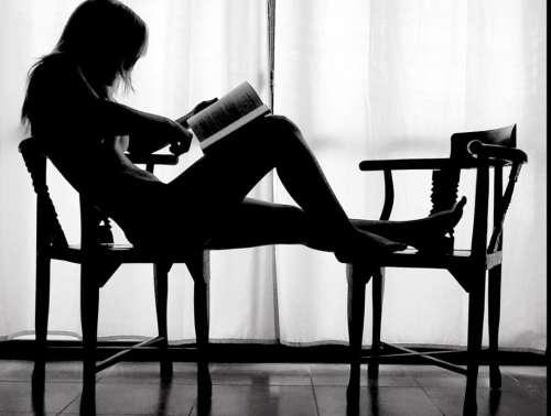 Mujer leyendo en una silla.