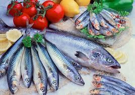 Diferentes pescados exhibidos con verduras