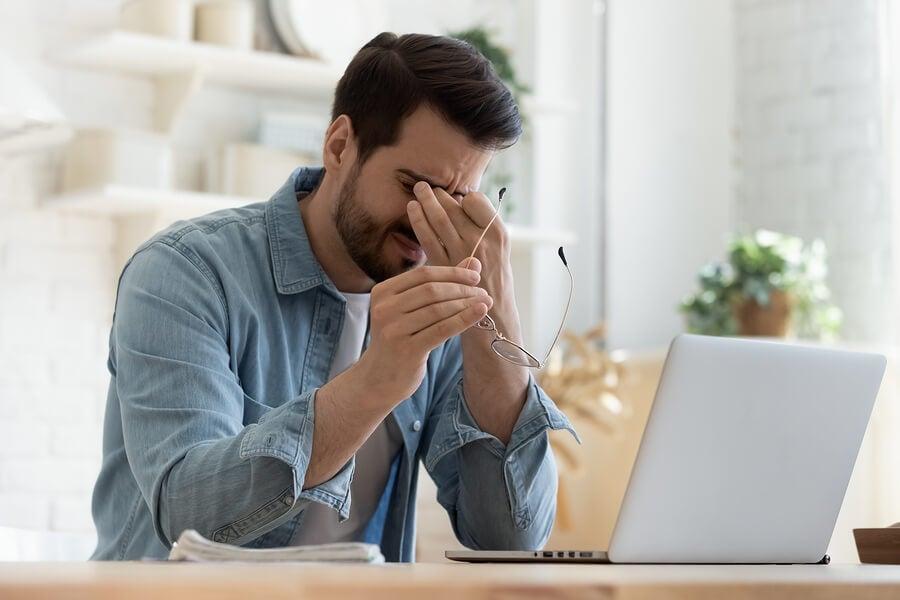 Hombre frente al ordenador con la vista cansada.