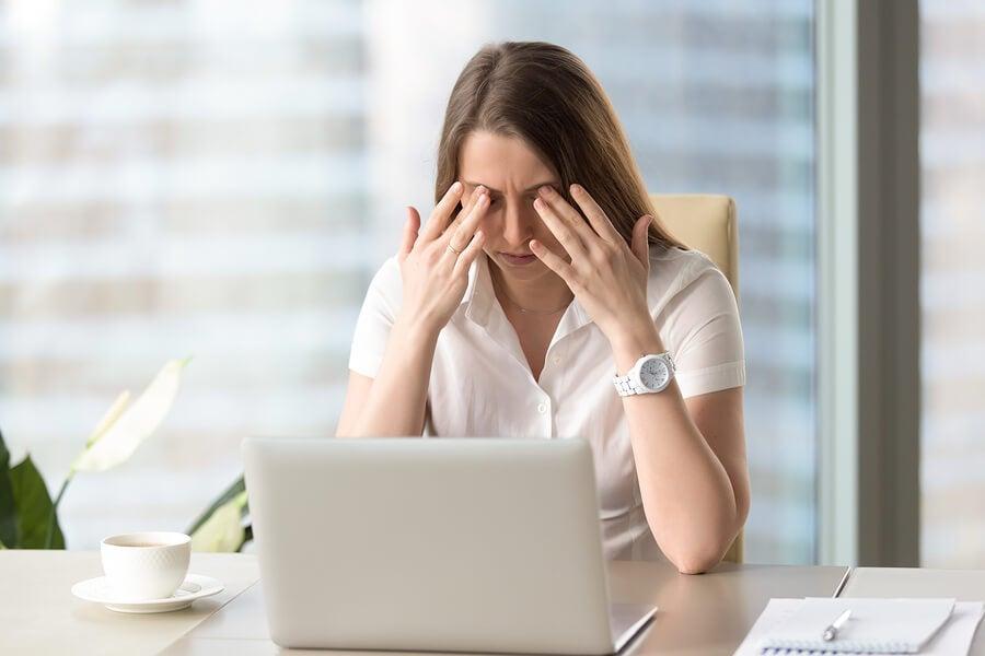 Mujer estresada frente al ordenador haciéndose un masaje en los ojos.
