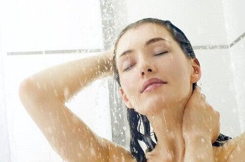 Mujer lavándose el cabello en la ducha.