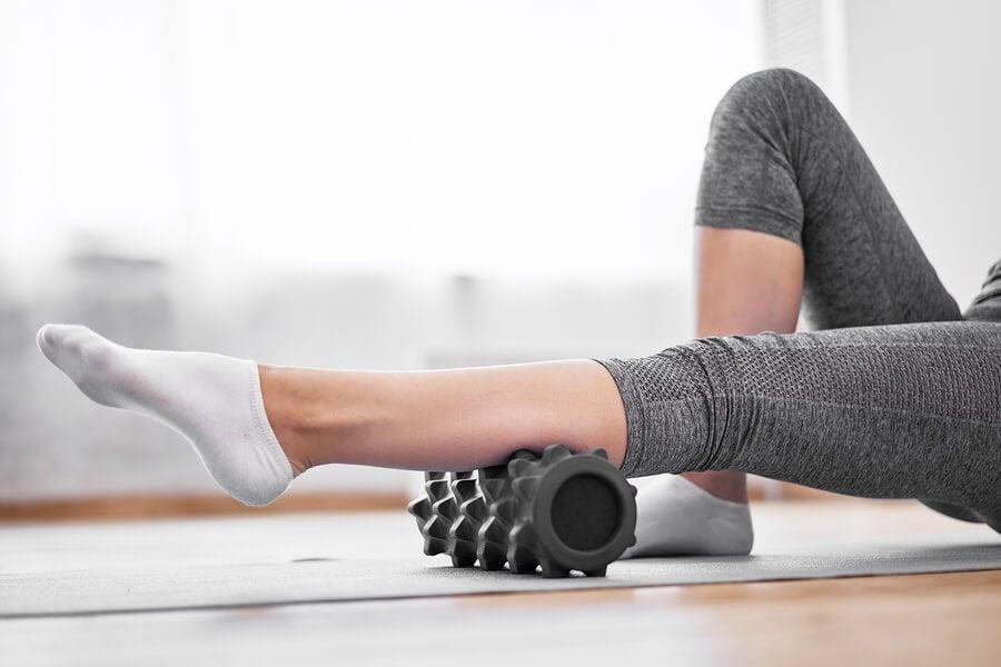 Mujer con rodillo masajeador en la pierna.