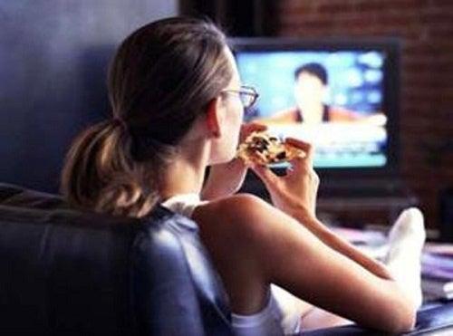Mujer comiendo frente al TV