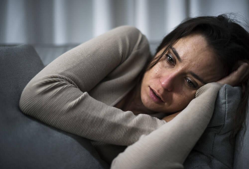 Mujer con depresión llorando en el sofá