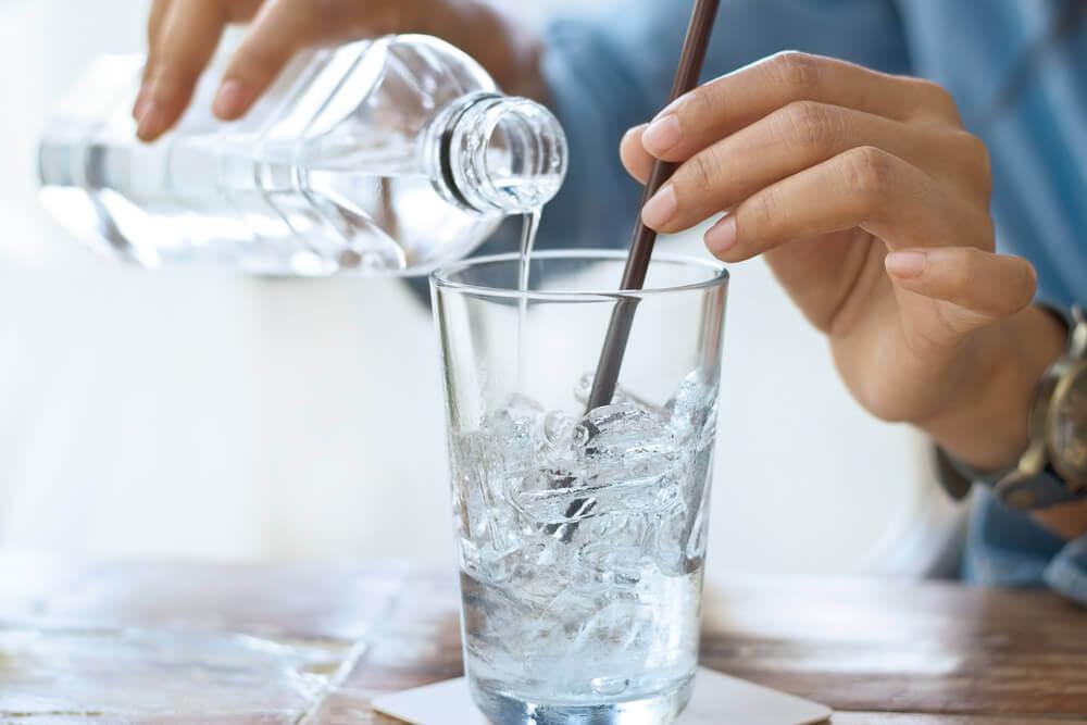 Mujer sirviendo un vaso de agua.