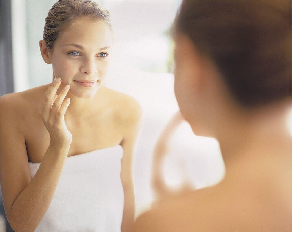 Mujer mirándose al espejo la piel después de haberse aplicado el agua de arroz.