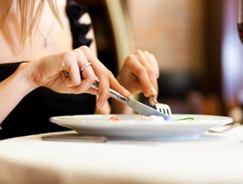 Manos de mujer cortando la comida de un plato.