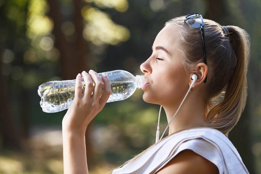 Chica bebiendo agua de una botella.
