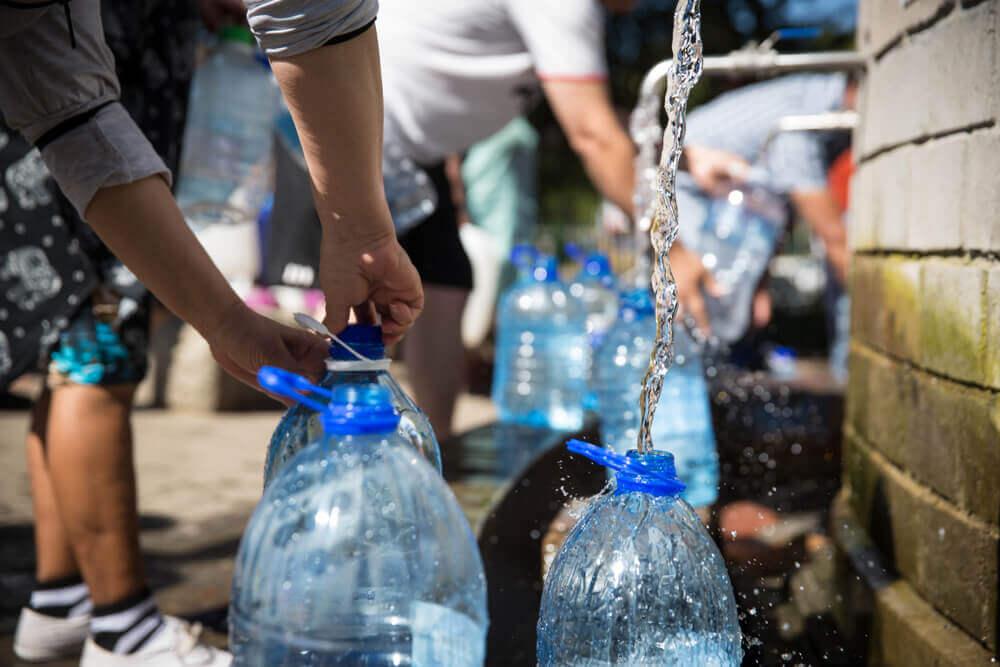 Personas rellenando botellas de plástico.