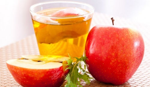 A glass of apple cider vinegar with two apples