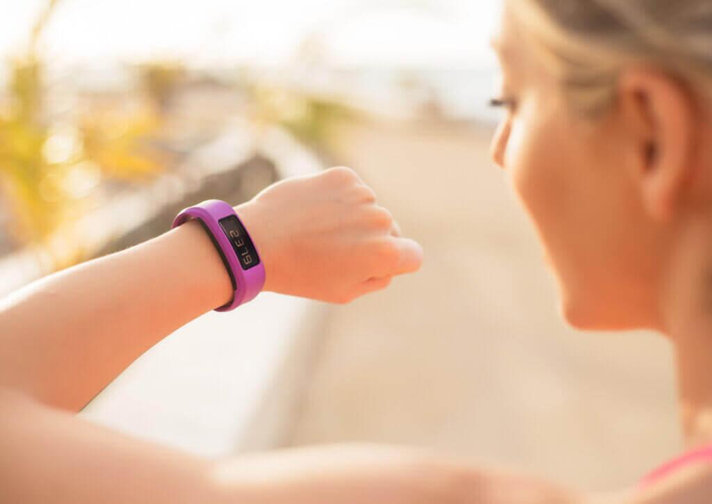 Mujer usando pulsera fitness para motivarse a volver a hacer ejercicio.