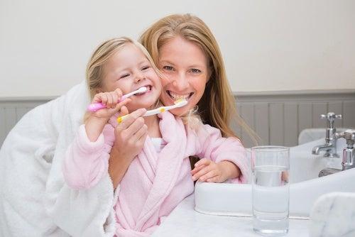 Madre e hija cepillándose los dientes: buena higiene bucal en los niños