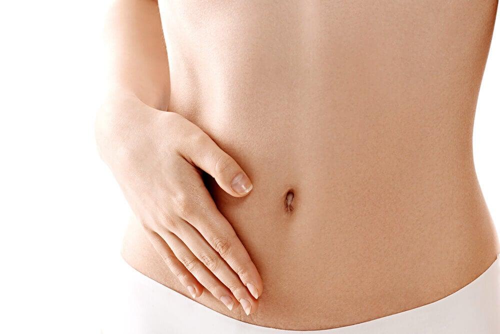 Mujer con la mano en el abdomen.